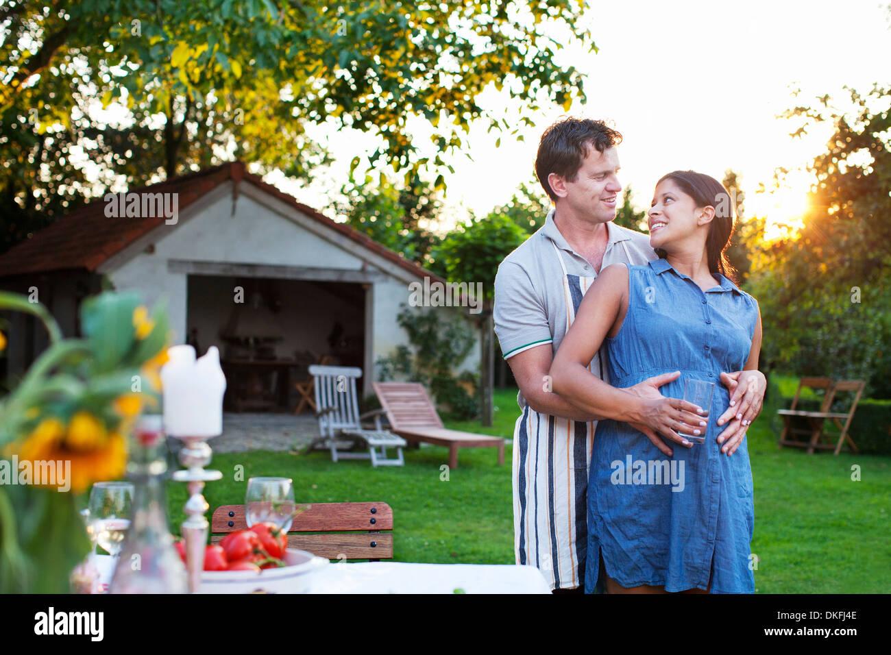 Abbracci uomo donna incinta, mani su stomaco Immagini Stock