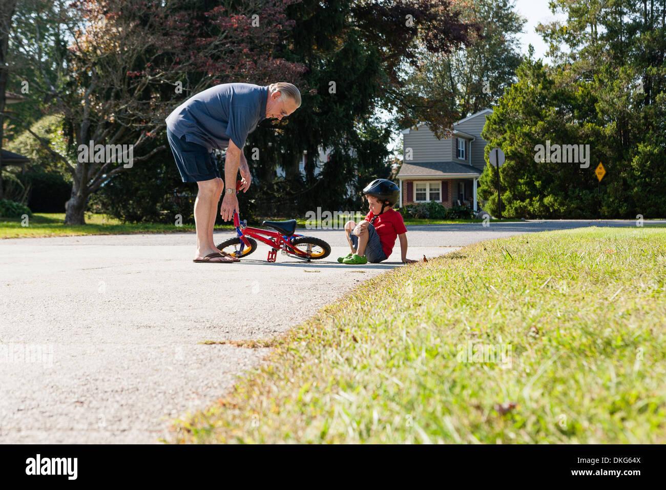 Il nonno di prelevare i ragazzi in bicicletta Immagini Stock