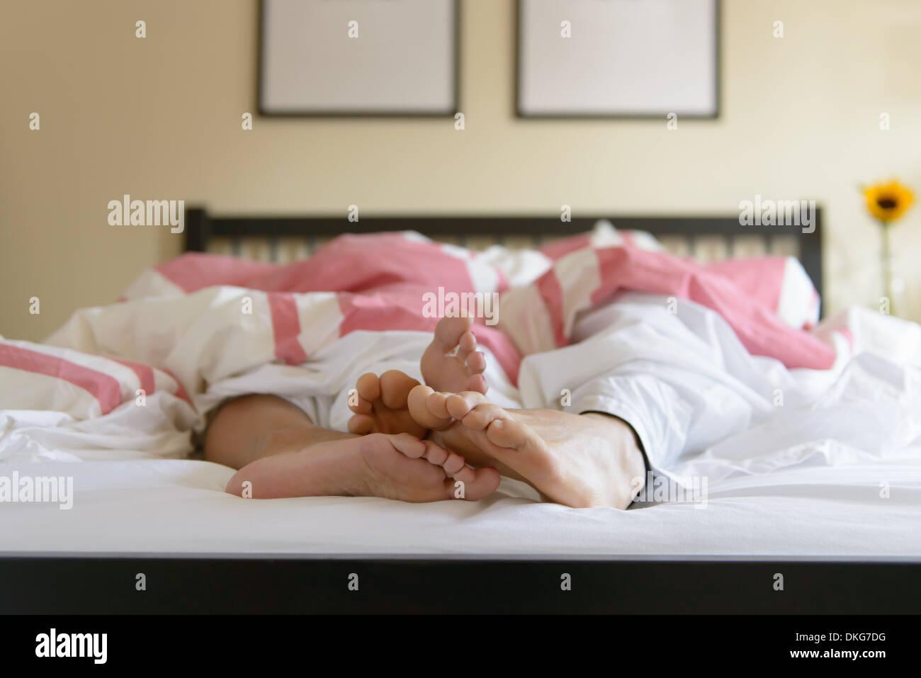 Superficie di livello immagine della coppia giovane a letto, in piedi fuori del piumone Immagini Stock