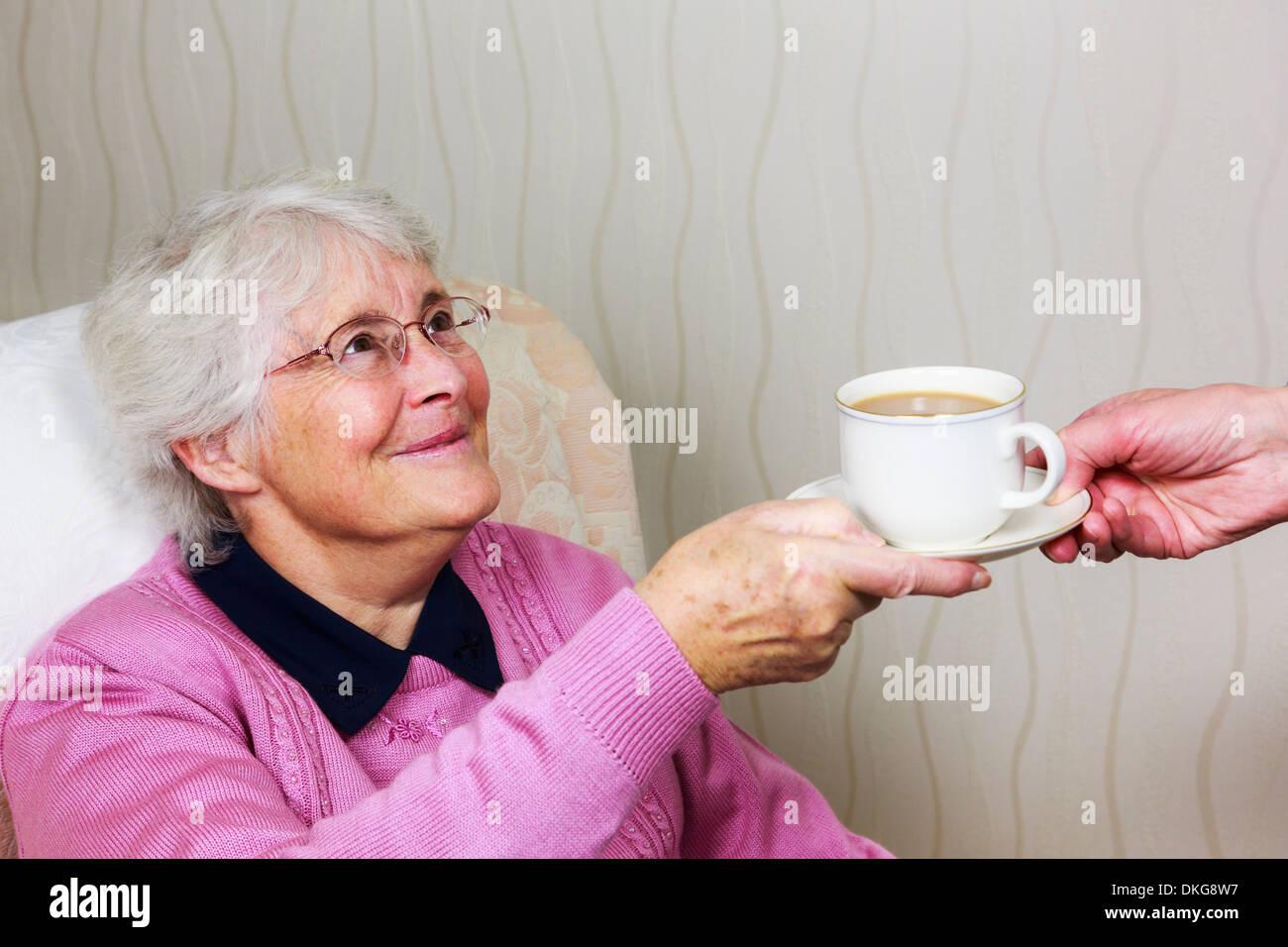 Fragile dolce felice vecchio anziani senior donna che guarda e sorridendo a un accompagnatore di consegnare la sua una tazza di tè durante la quotidiana cura quotidiana home visita. Inghilterra, Regno Unito Immagini Stock