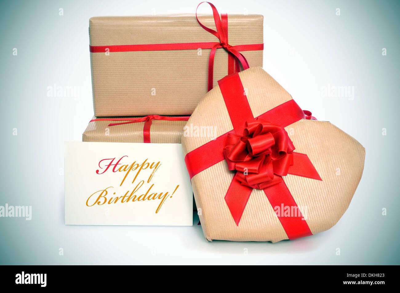 Alcuni doni, uno di essi a forma di cuore, e il testo happy birthday scritto in un cartello Immagini Stock