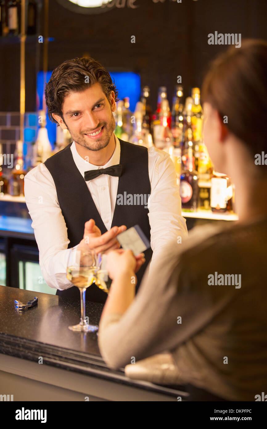 Ben vestito barista prendendo carta di credito dal cliente nel bar di lusso Immagini Stock