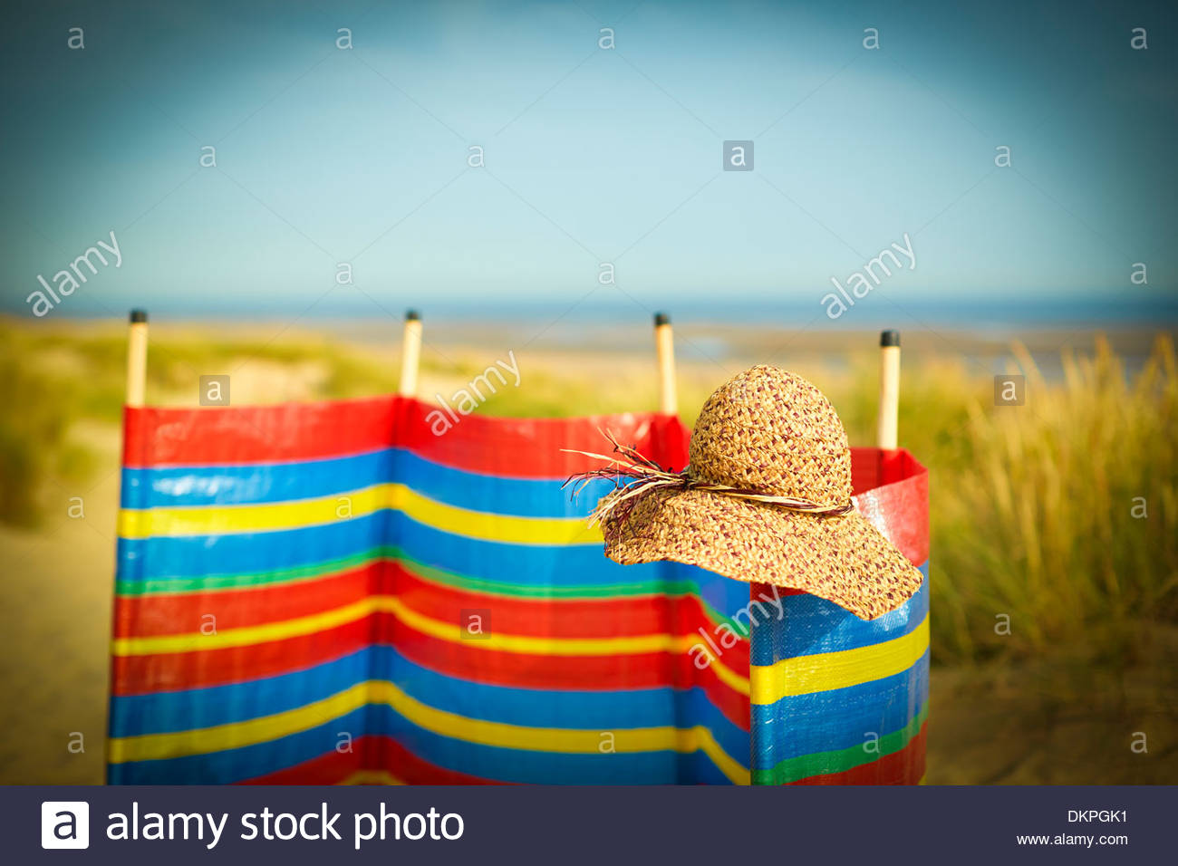 Cappello di paglia sulla barriera di vento sulla spiaggia Immagini Stock