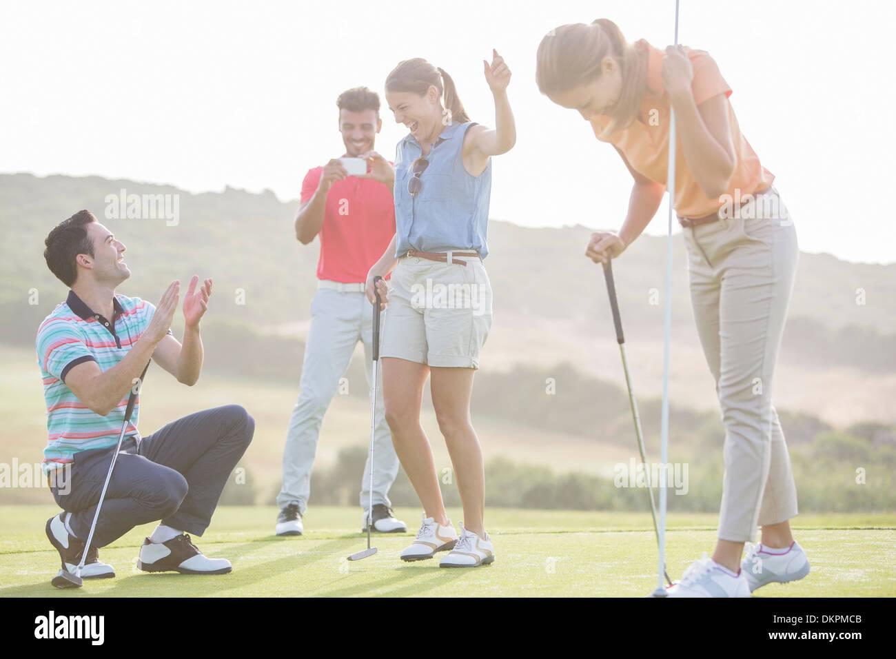 Amici per giocare a golf sul corso Immagini Stock