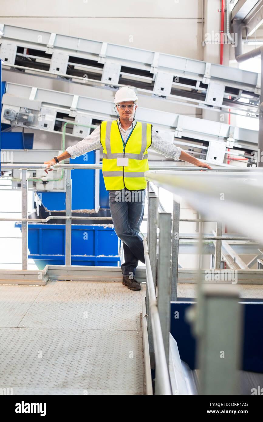 Lavoratore appoggiata sulla ringhiera della piattaforma in fabbrica Foto Stock