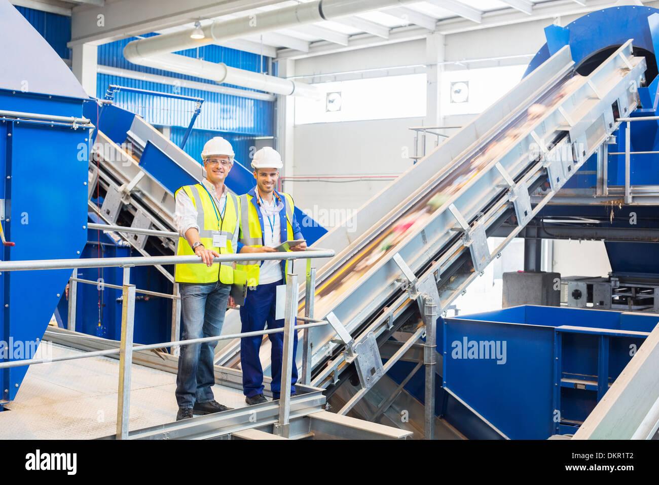 Lavoratori sorridente nel centro di riciclaggio Foto Stock