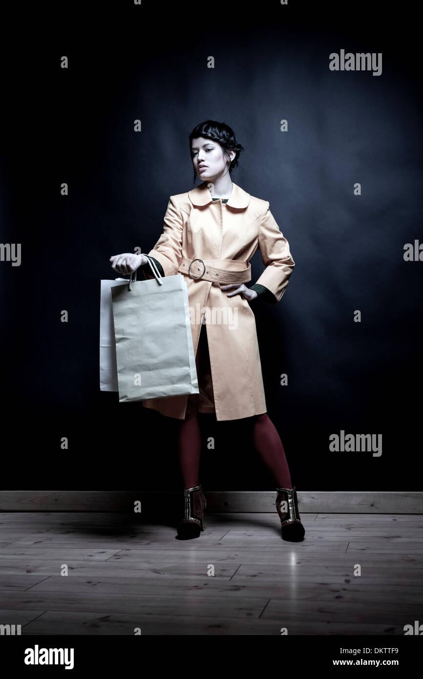 Giovane donna con le borse della spesa e la mano sul Hip Immagini Stock