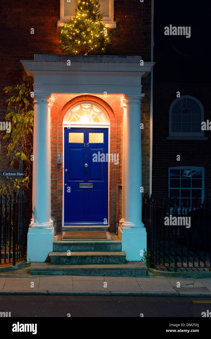 Un illuminato porta blu e il portico di ingresso a una proprietà in stile georgiano, Arundel, West Sussex, Regno Unito Immagini Stock