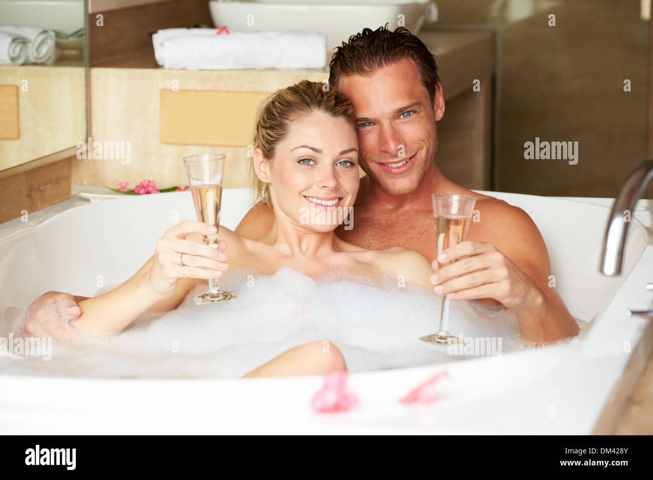 Bagno Romantico In Due giovane relax nella vasca da bagno di bere champagne insieme