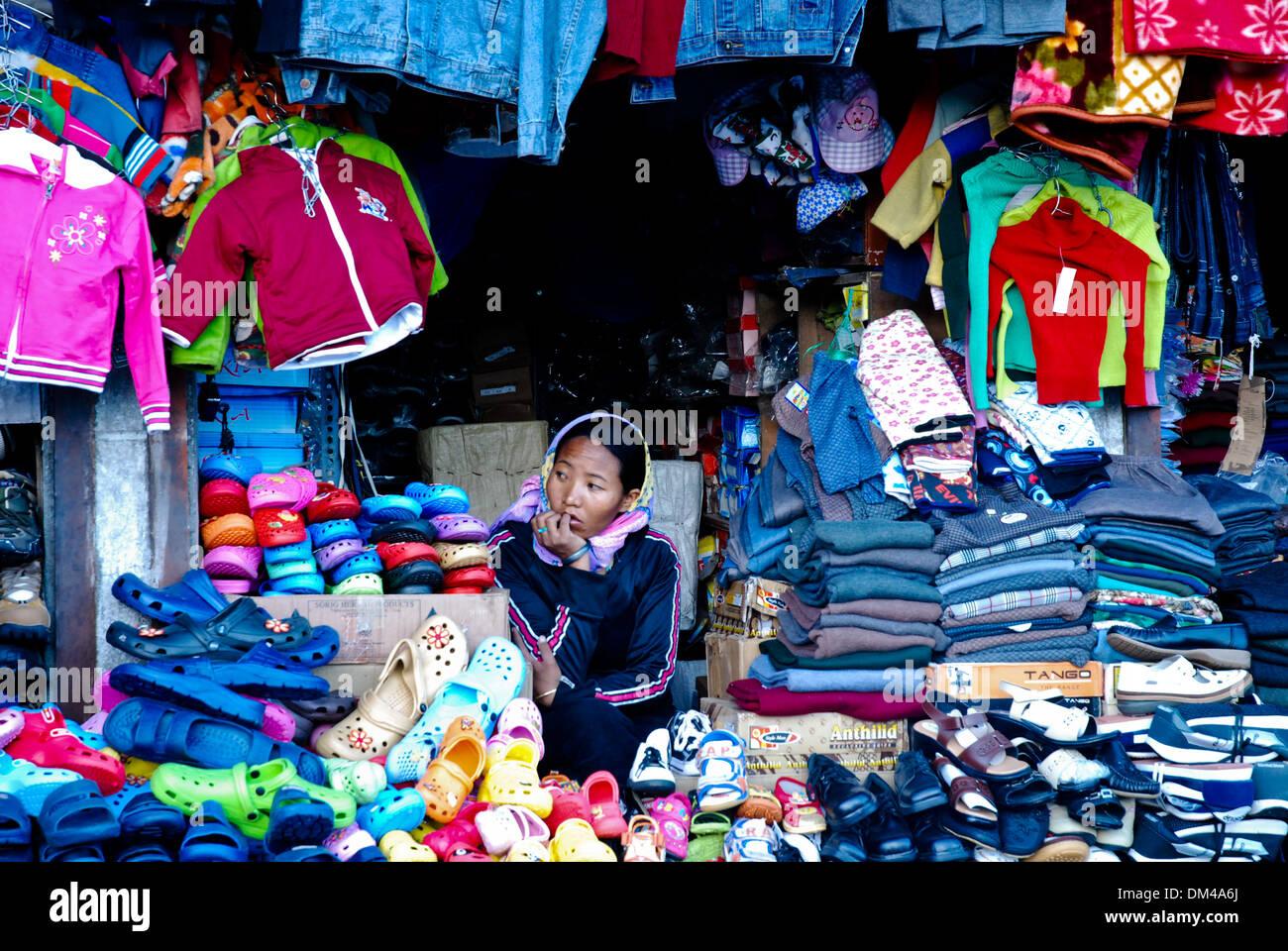 Ladakh, India - 16 Luglio 2009: una donna si siede in attesa per il cliente successivo in un colorato negozio di abbigliamento in Leh. Immagini Stock
