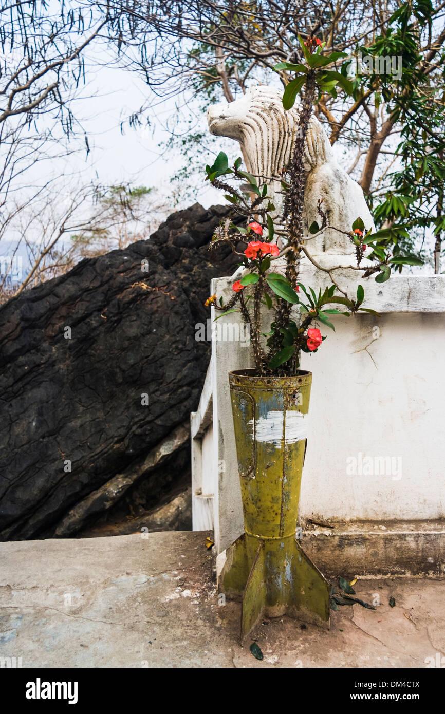 Guscio di bomba riciclato in un vaso da fiori davanti a un monastero buddista in Luang Prabang. Laos. Immagini Stock