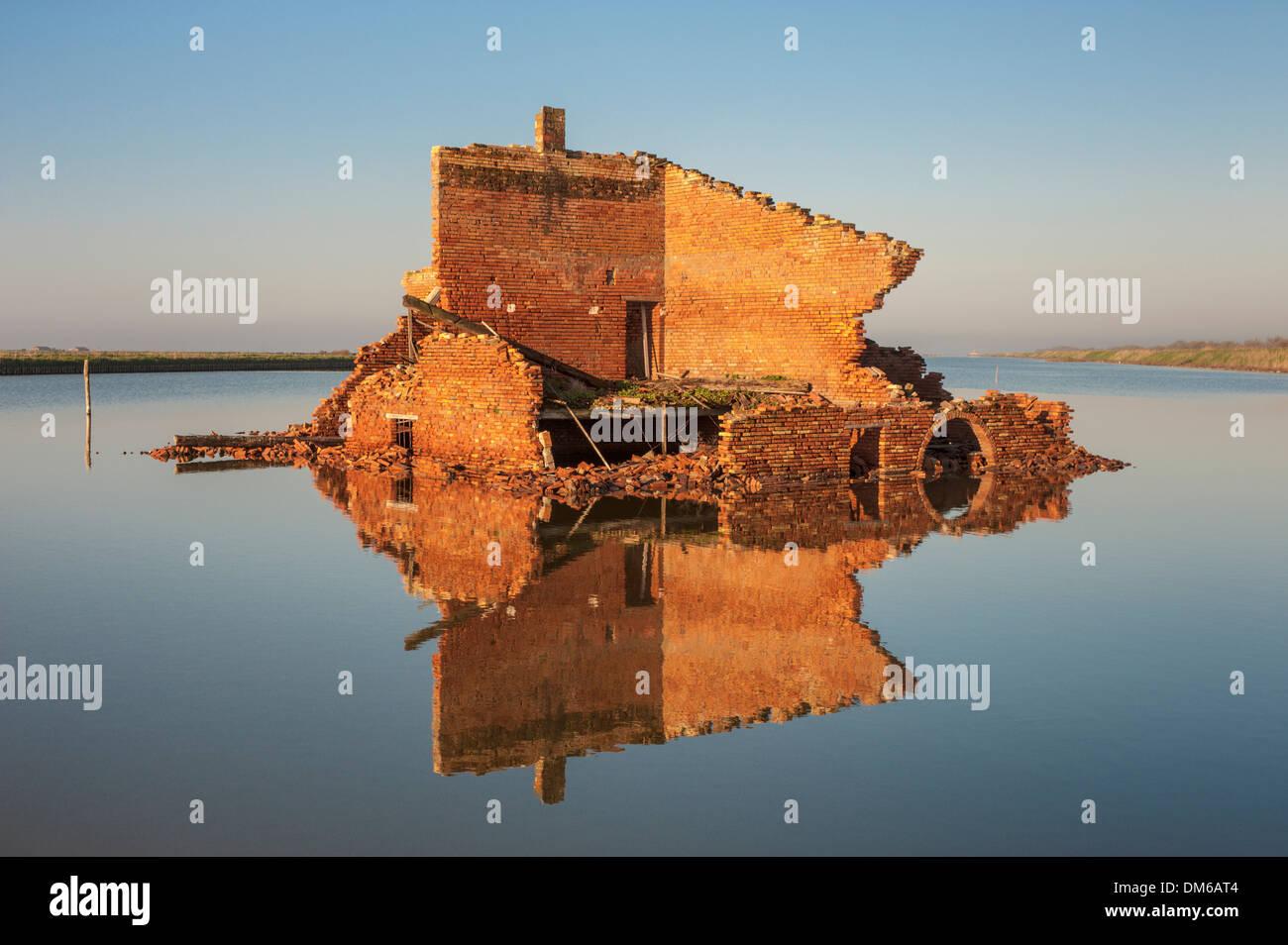 Resti fuori da un edificio in mattoni rossi in una laguna, con riflessioni, Delta del Po, Comacchio, Emilia Romagna, Italia Immagini Stock