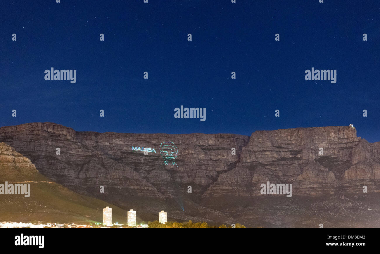 Cape Town, Sud Africa, giovedì 12 dicembre 2013: un laser contorno immagine di Nelson Mandela è proiettata sulla Montagna della Tavola durante la notte in onore di lui dopo la sua morte il 5 dicembre 2013. Madiba è stato il suo nome del clan e il nome con il quale egli è stato spesso affrontato. Credito: Eric Nathan/Alamy Live News Immagini Stock