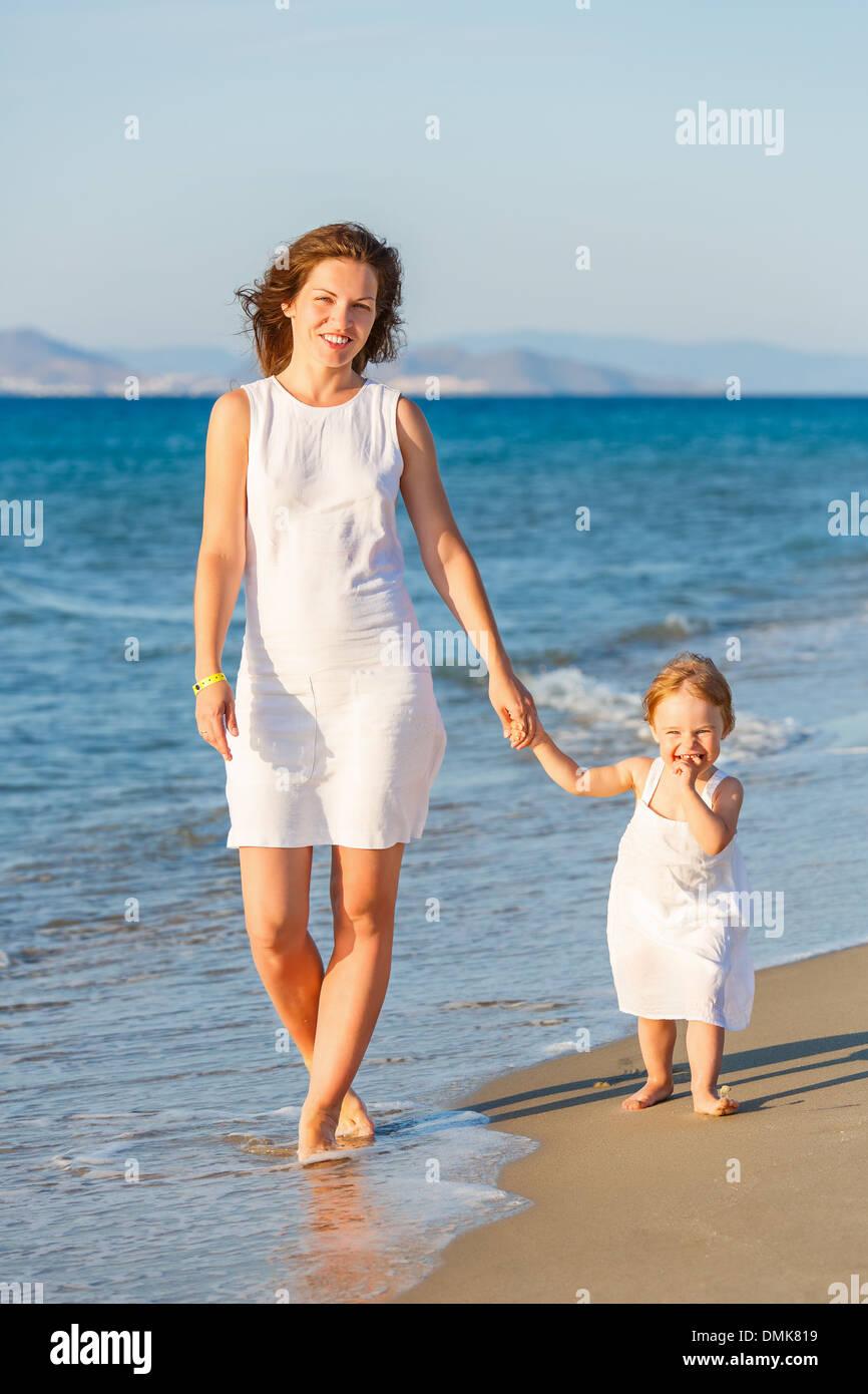 Madre e figlia di camminare sulla spiaggia Foto Stock