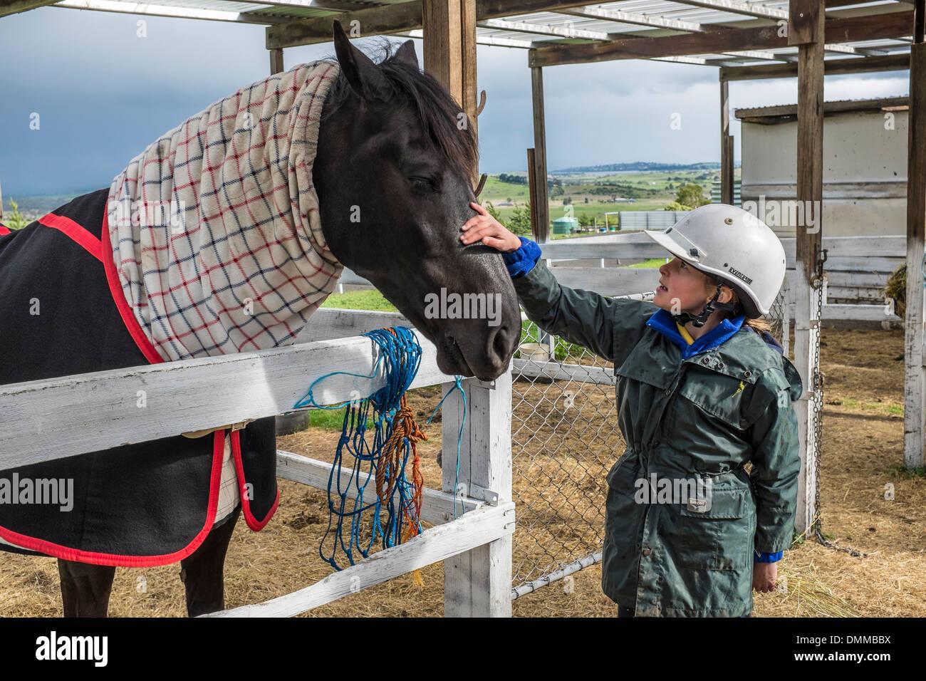 Una giovane ragazza di conoscere un cavallo presso una scuola di equitazione in Tasmania Australia Immagini Stock