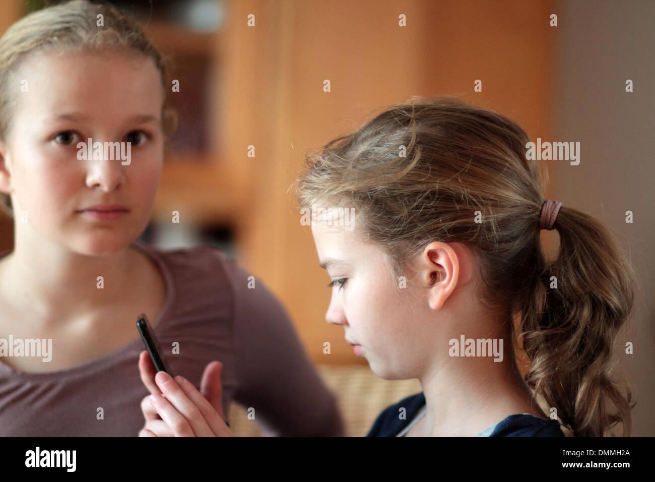 Le ragazze alla ricerca di un telefono in una sala insieme Immagini Stock