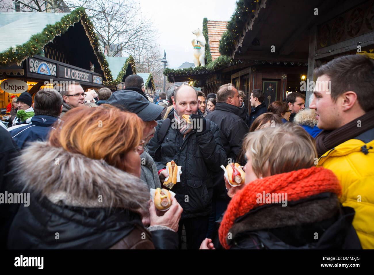 Il mercatino di Natale di Colonia: persone mangiare salsiccia rotolo all'Altstadt o la parte vecchia della città Immagini Stock