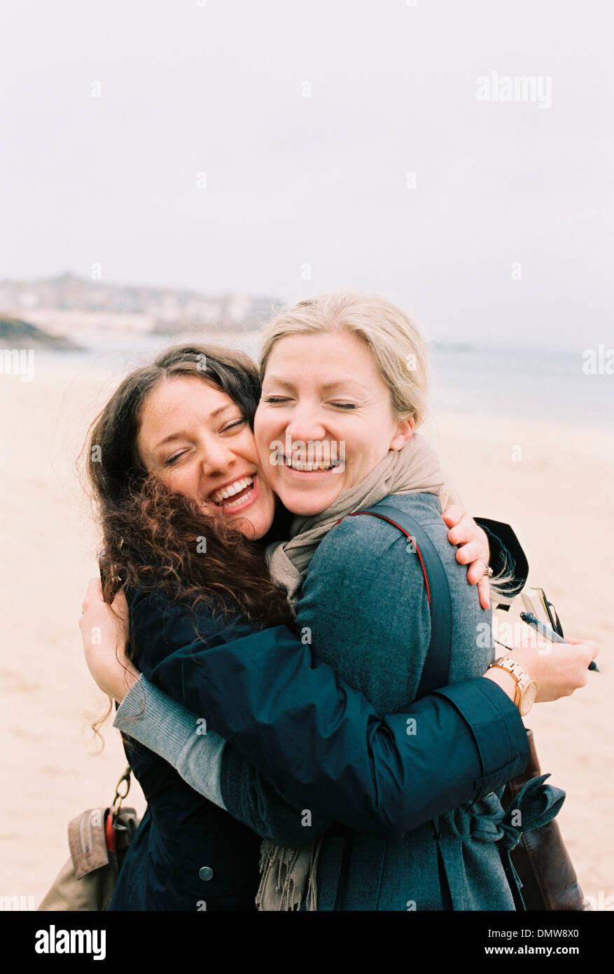 Due donne guancia a guancia avvolgente su una spiaggia. Immagini Stock