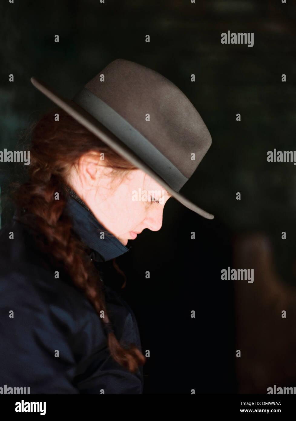 Profilo di una donna che indossa un cappello di feltro con un orlo. Immagini Stock