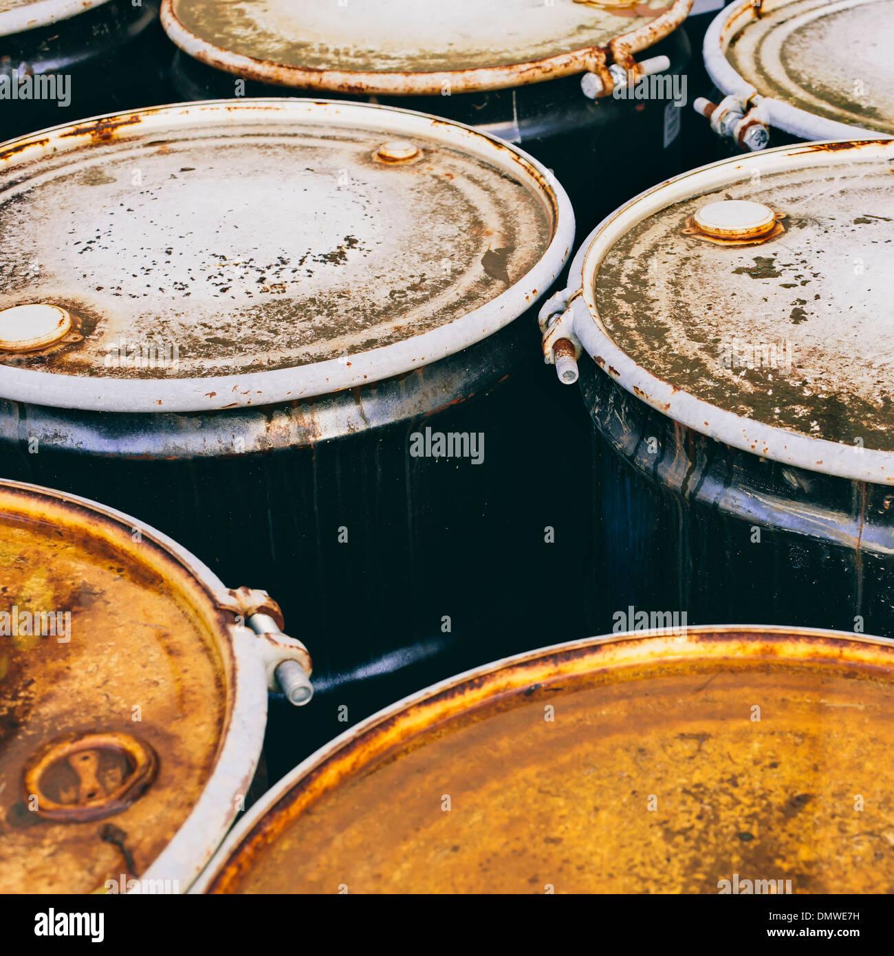 Un gruppo di arrugginita corroso barili di chimica o di prodotti petroliferi. Immagini Stock