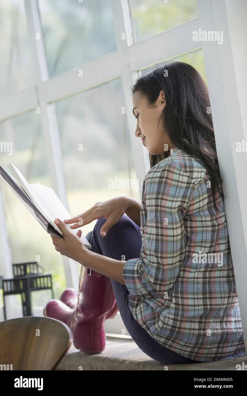 Una giovane donna seduta a leggere un libro. Immagini Stock