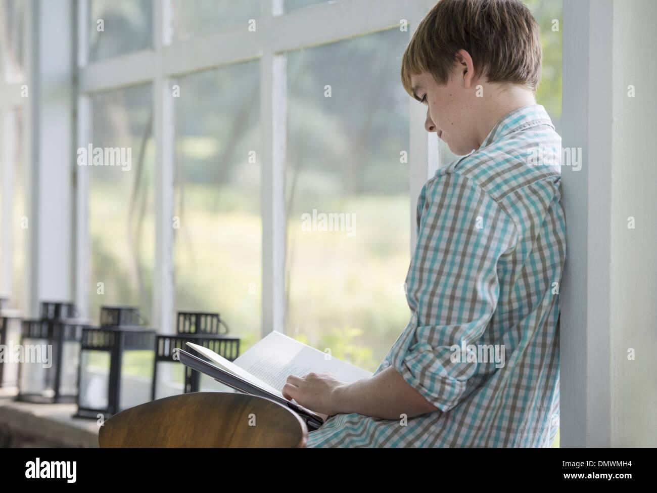Un giovane persona seduta a leggere un libro. Immagini Stock