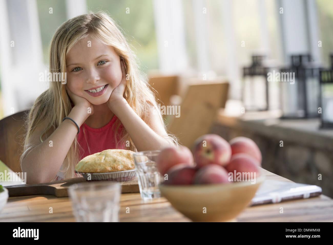 Una giovane ragazza guardando una torta di pasticceria sorridente. Immagini Stock