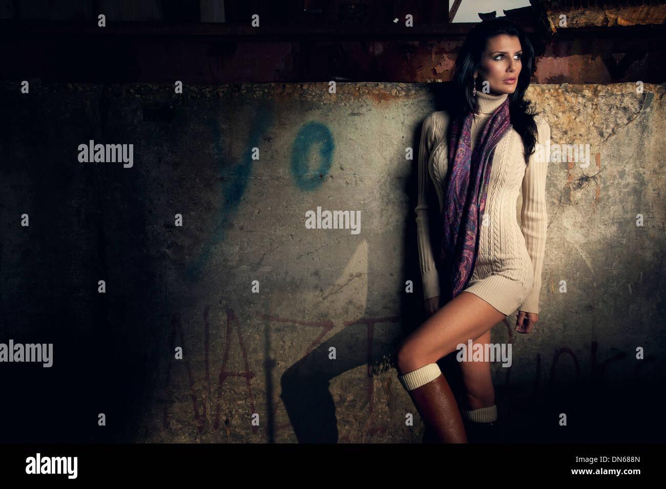 Moda ritratto di donna in piedi nel magazzino abbandonato in abito corto Immagini Stock