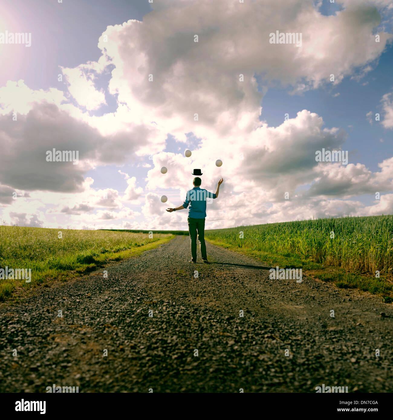 Giovane uomo con cappello galleggiante giocoleria nel campo Immagini Stock