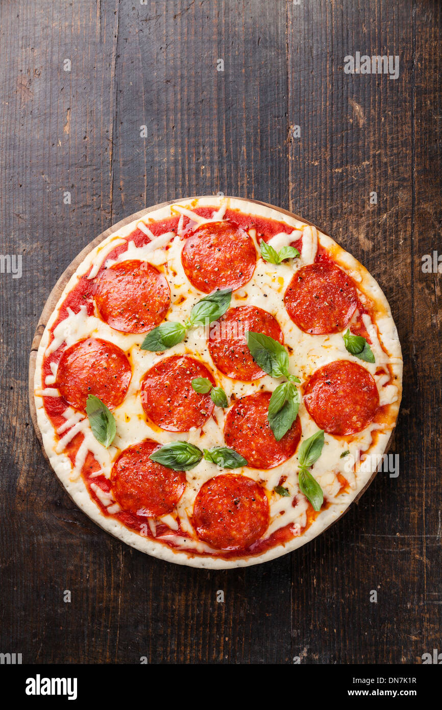 Salsiccia per Pizza Pizza con le foglie di basilico sul tavolo di legno Immagini Stock