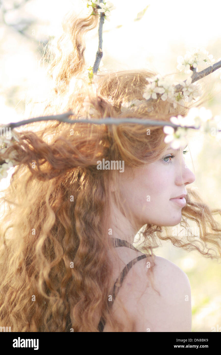 Donna con capelli lunghi tra rami fioriti, ritratto Immagini Stock