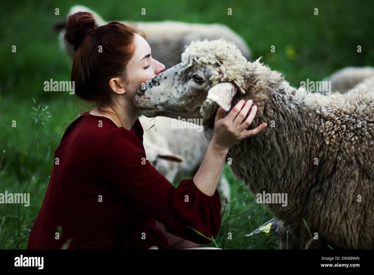 Giovane donna con pecora su un prato Immagini Stock