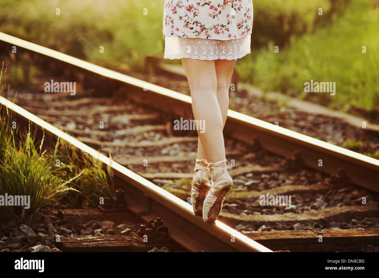 Giovane donna abito in equilibrio su un binario ferroviario Immagini Stock