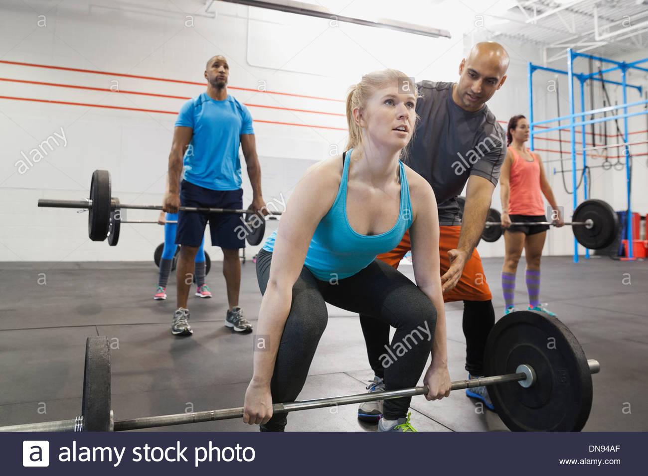 Istruttore di palestra ad assistere la donna con tecnica deadlift Immagini Stock