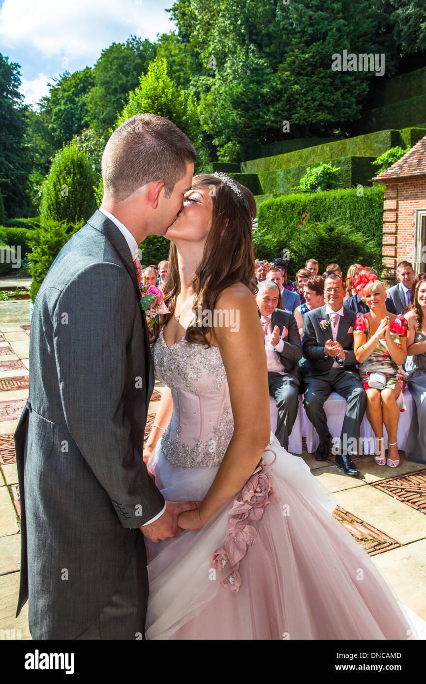Primo bacio tra la sposa e lo sposo Foto Stock