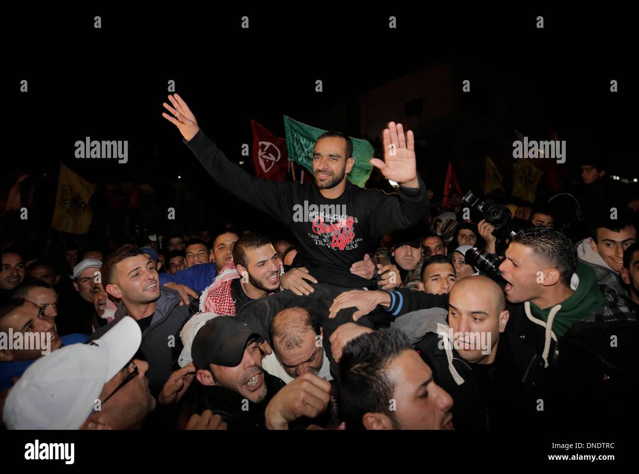 Gerusalemme. 23 Dic, 2013. Palestinesi portano rilasciato prigioniero palestinese Samer Essawi (C) come si celebra nella città Essaweyeh a Gerusalemme est, a Dic. 23, 2013. Le autorità israeliane lunedì rilasciato Samer Essawi, un prigioniero palestinese che è andato su il più lungo sciopero della fame contro Israele, dopo oltre 17 mesi di carcere, la sua famiglia ha detto ai giornalisti. Credito: Muammar Awad/Xinhua/Alamy Live News Immagini Stock