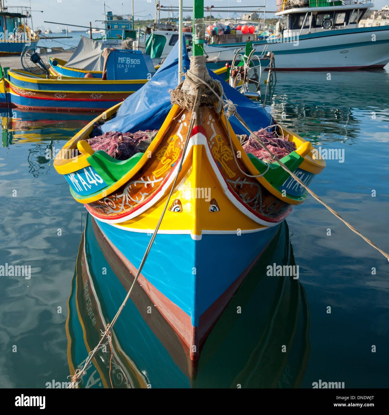 Un colorato luzzu ormeggiata nel porto di Marsaxlokk di Marsaxlokk, Malta. Un luzzu è un maltese tradizionale barca da pesca. Immagini Stock