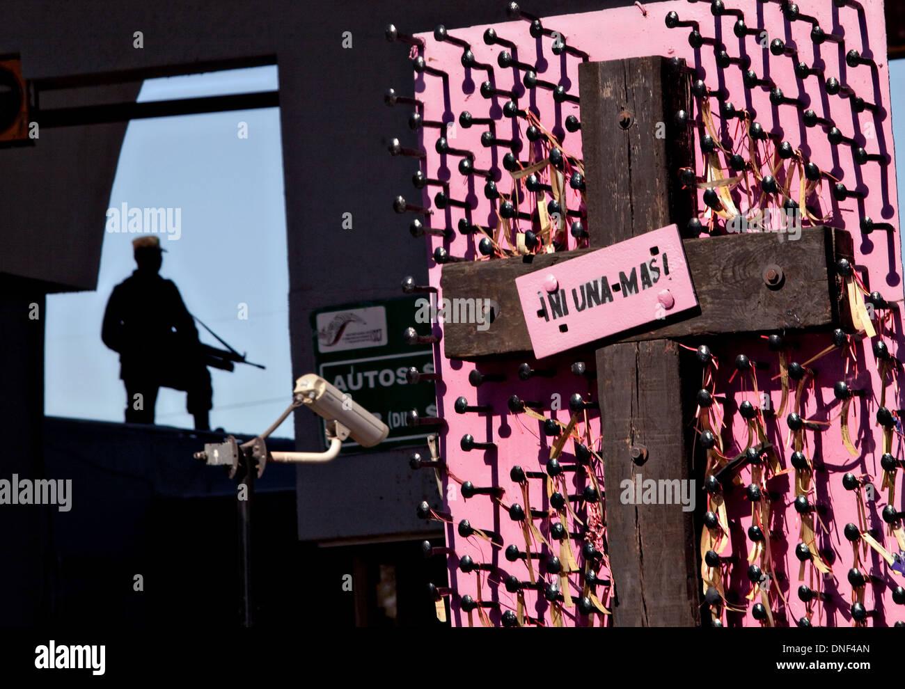 """Un soldato si profila all'Juarez Avenue valico di frontiera negli Stati Uniti come da un memoriale per le donne uccise in atti di violenza in Juarez, Messico 14 gennaio 2009. Il cartello dice """"non uno di più' in riferimento alle vittime della droga in corso della guerra che ha già fatto più di quaranta persone dall'inizio dell'anno. Più di 1600 persone sono state uccise in Juarez nel 2008, rendendo Juarez la città più violenta del Messico. Immagini Stock"""
