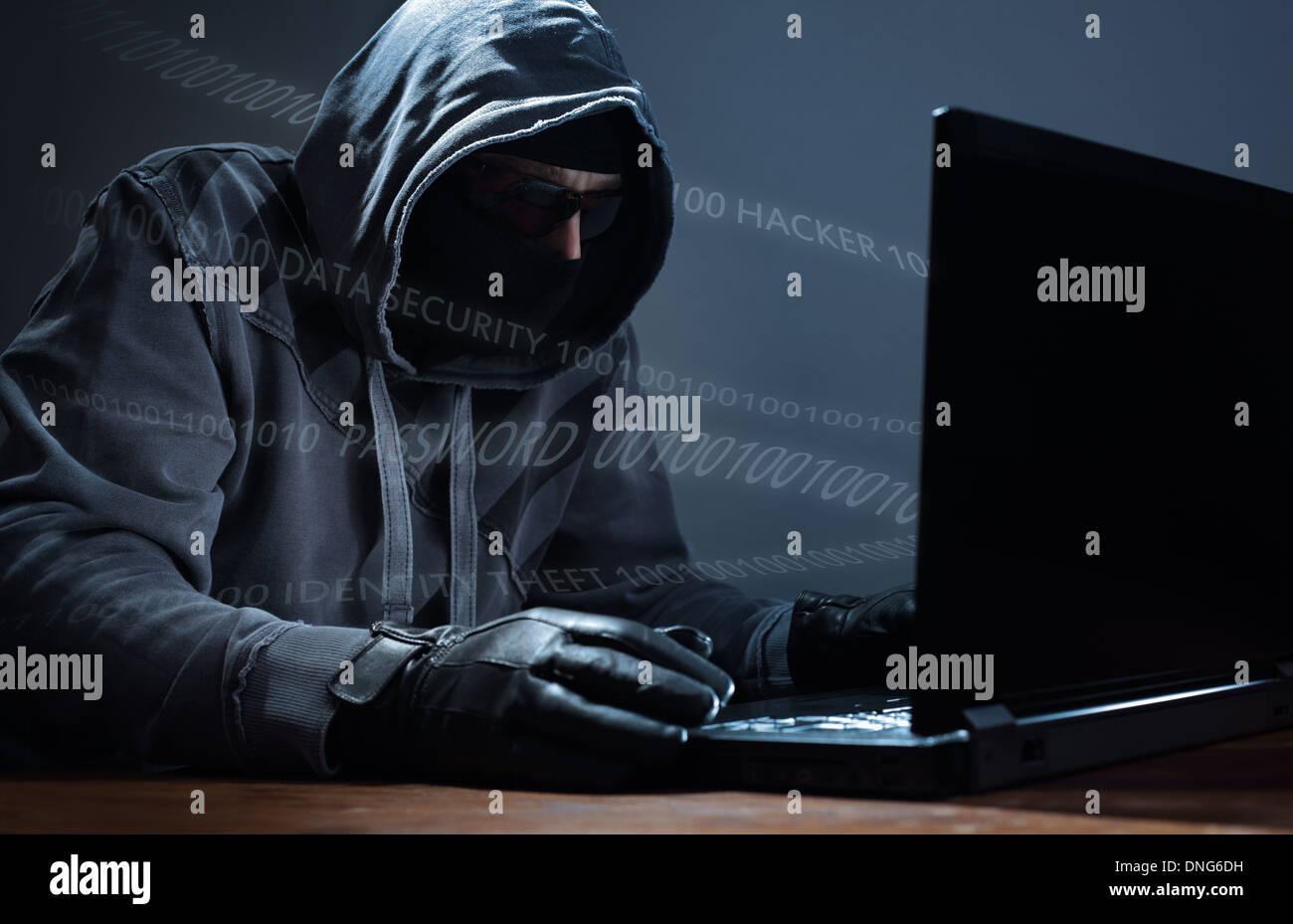 Il pirata informatico di rubare i dati da un computer portatile Immagini Stock