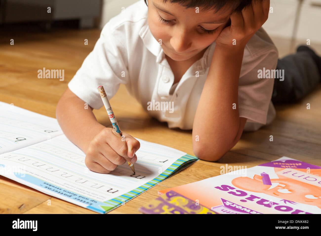 Ragazzo giovane imparare il suo alfabeto Immagini Stock