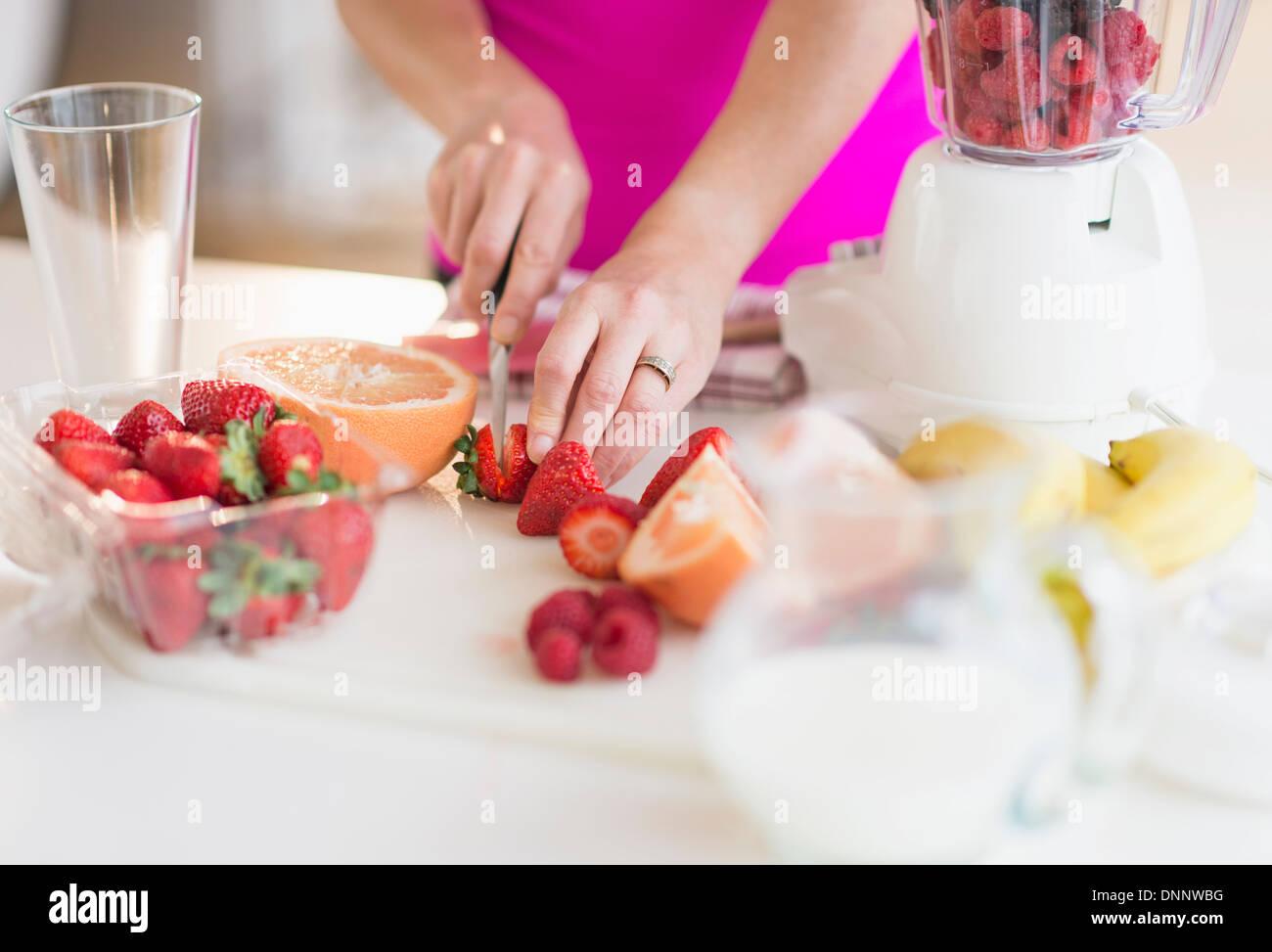 La donna per affettare le fragole Immagini Stock