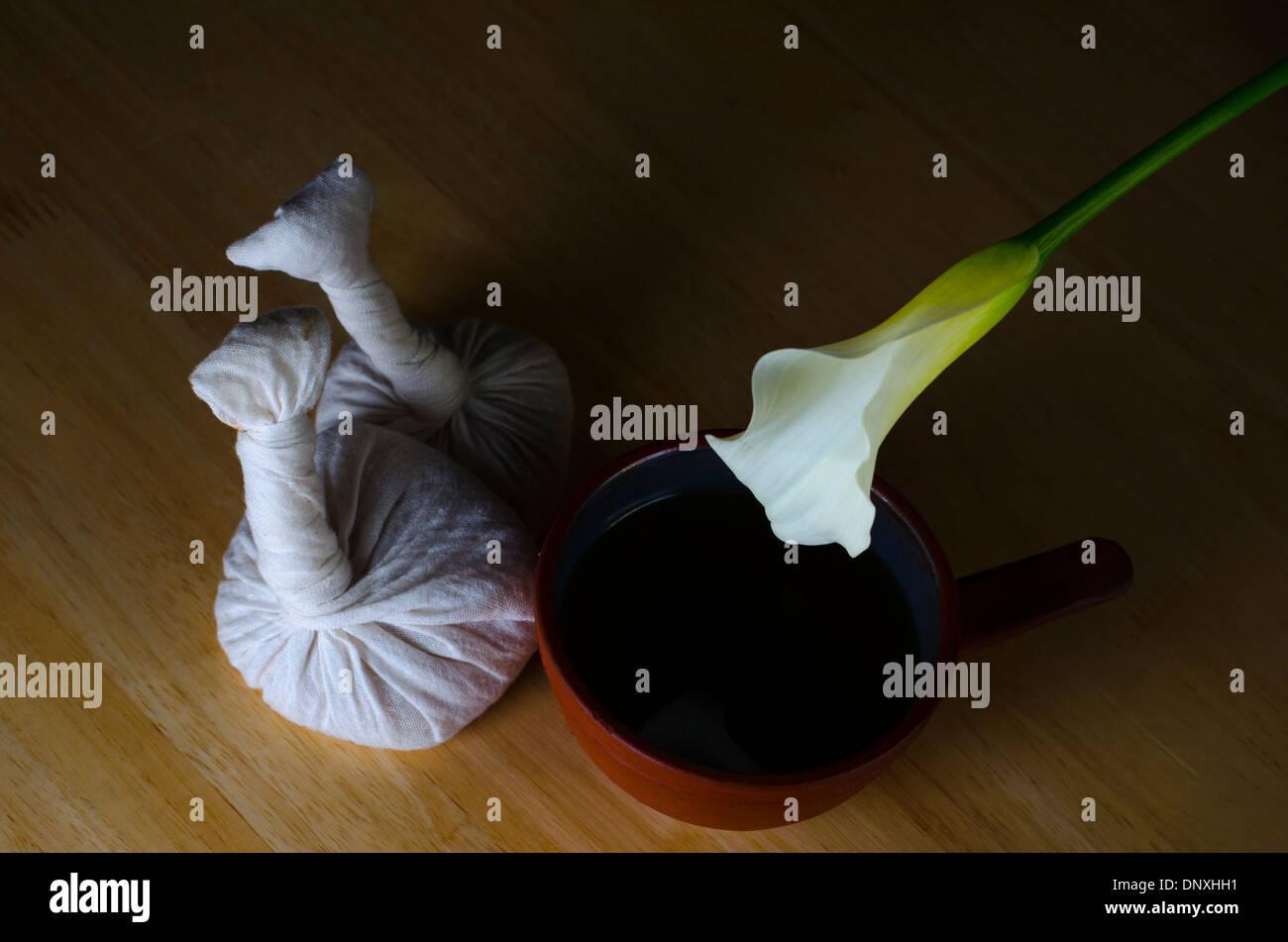 Il piano di un tavolo disposizione di massaggio ayurvedico con olio cataplasmi e esotico fiore bianco. Immagini Stock