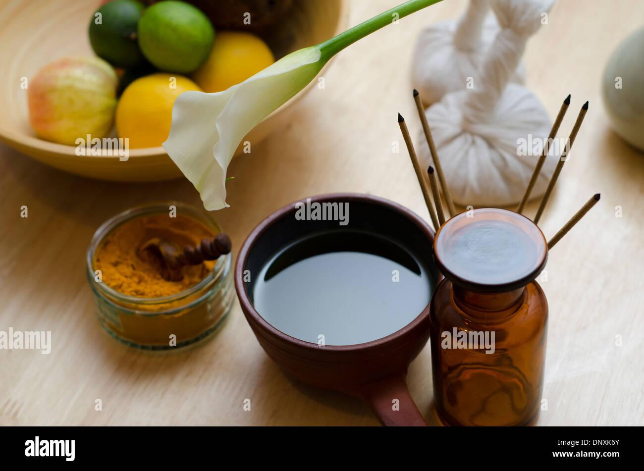 Una disposizione del piano del banco di ayurveda di curcuma spezie, olio e strumenti di massaggio e un esotico fiore utilizzato nel massaggio Ayurveda. Immagini Stock