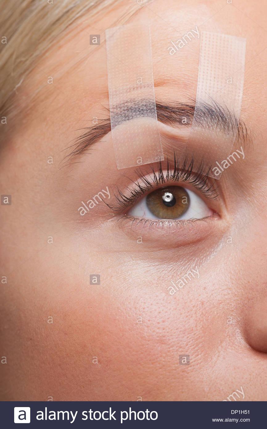 Close up di donna con gli occhi aperti con nastro adesivo Immagini Stock