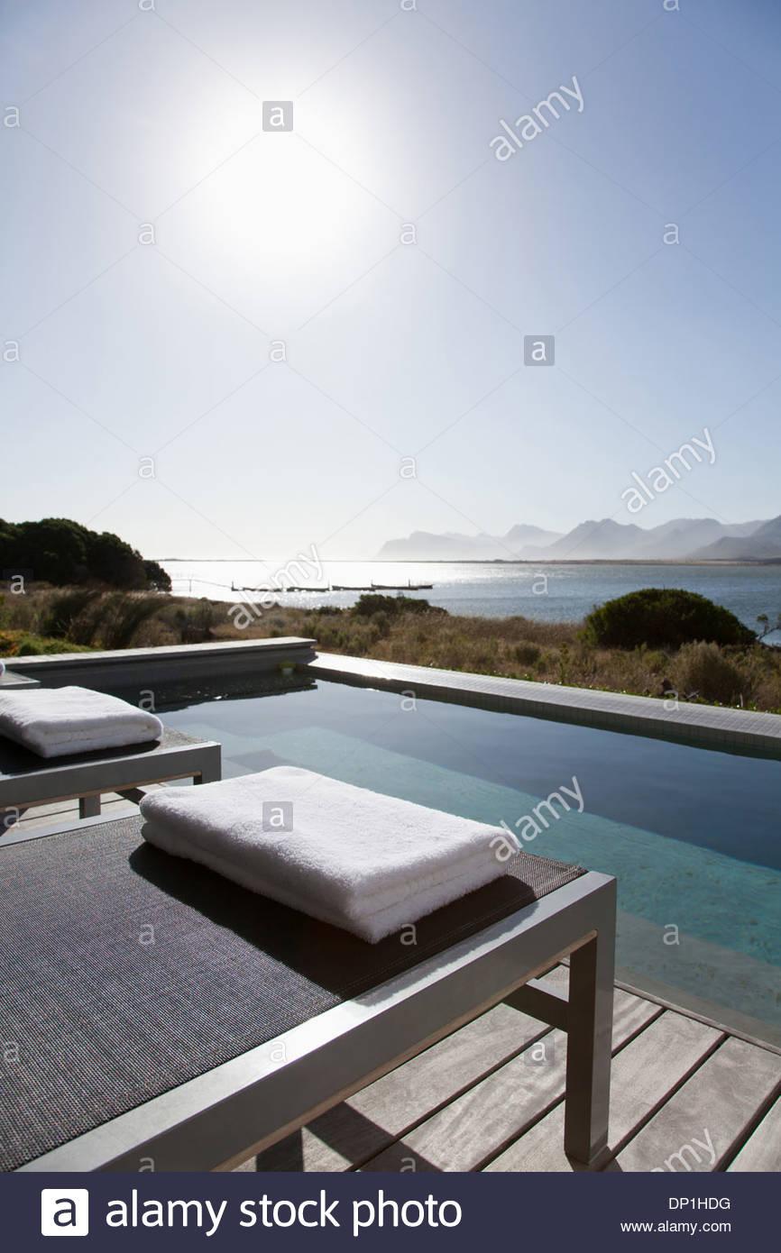 Vista del sole che splende sul lago dal patio con piscina Immagini Stock