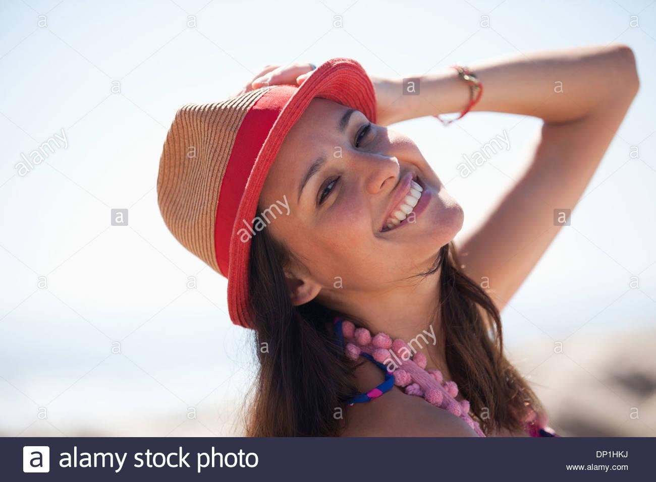Donna sorridente indossando cappello per il sole sulla spiaggia Immagini Stock
