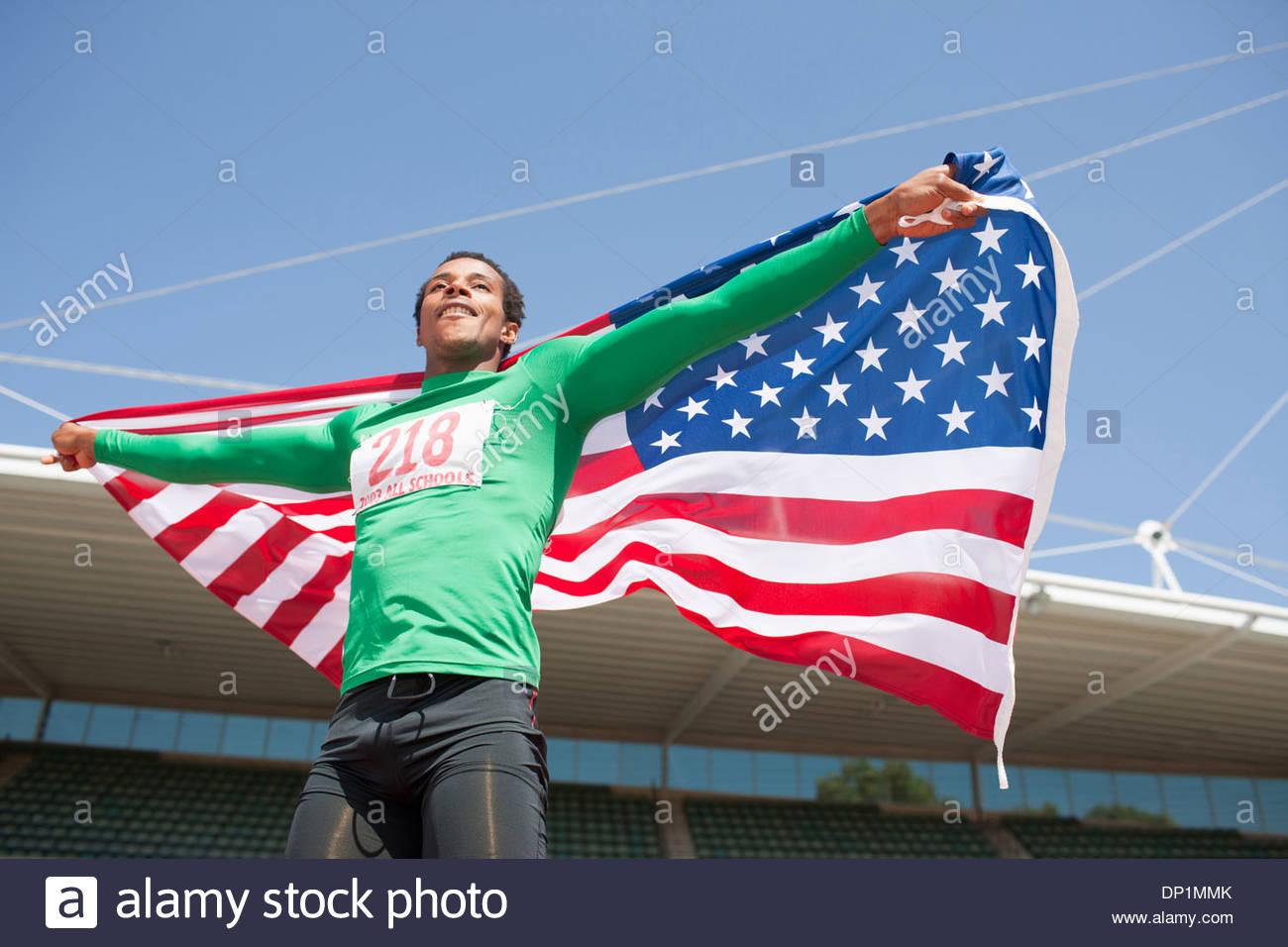 Runner celebrando in pista con la bandiera americana Immagini Stock