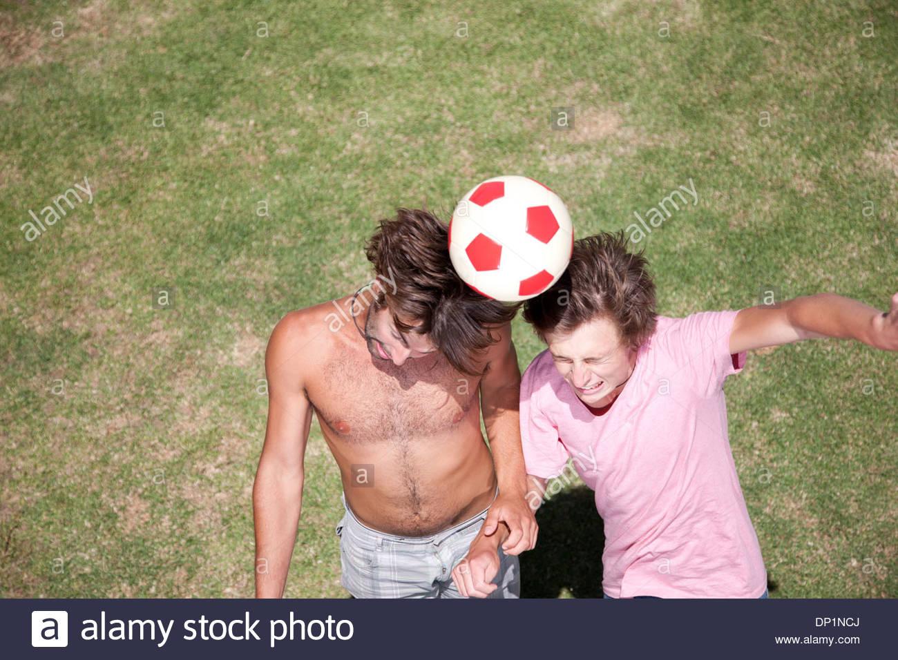 Gli uomini che giocano a calcio in erba Immagini Stock
