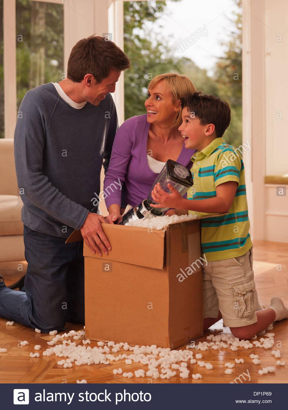 Famiglia apertura della casella nel soggiorno Immagini Stock