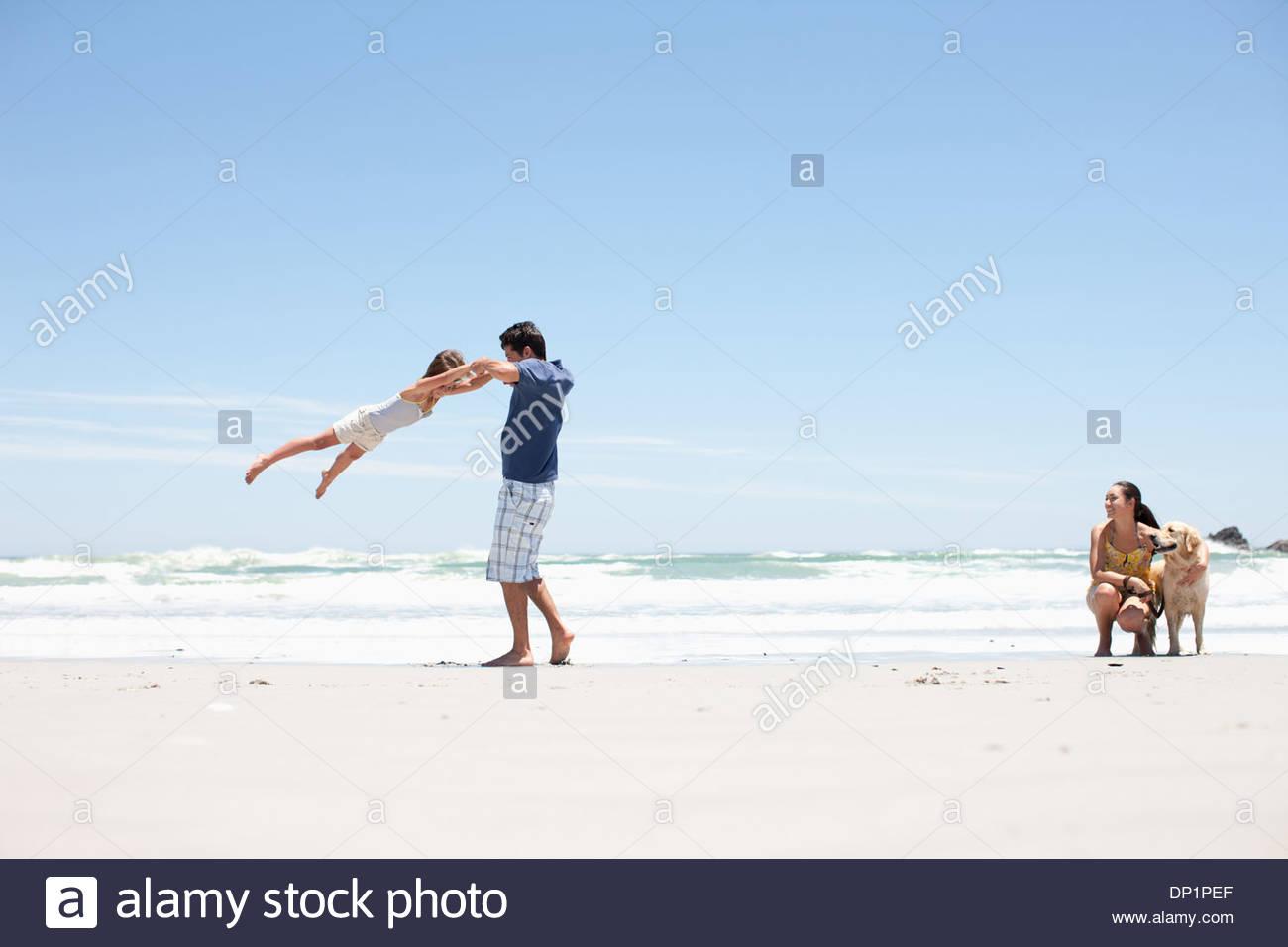Famiglia con il cane a camminare sulla spiaggia Immagini Stock